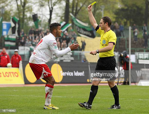 Referee Karl Valentin shows the yellow card to Phil OfosuAyeh of Erfurt during the 3rd Liga match between RW Erfurt and Preussen Muenster at...