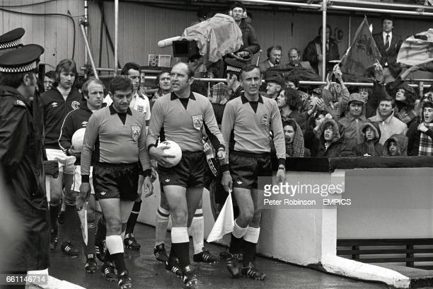 Referee Karoly Palotai leads the teams out followed by Scotland captain Archie Gemmill and goalkeeper Alan Rough