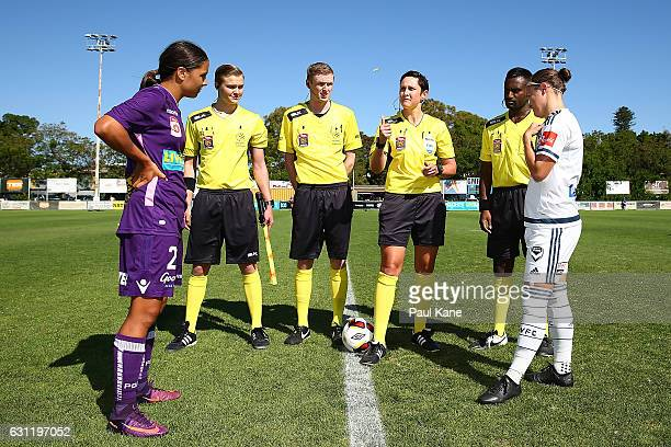 Referee Kate Jacewicz tosses the coin as captains Samantha Kerr of the Glory and Christine Nairn of the Victory look on during the round 11 W-League...