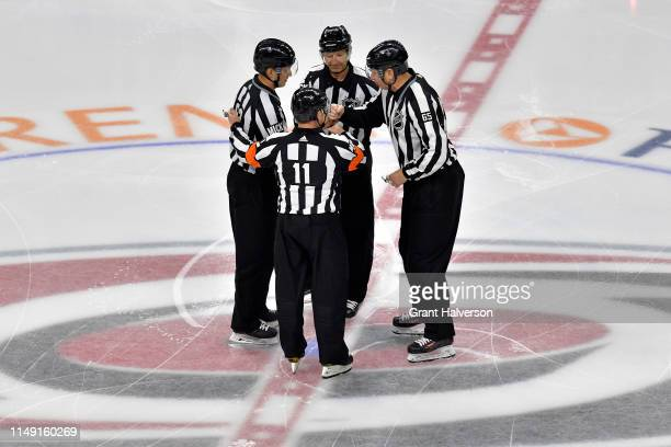 Referee Kelly Sutherland linesman Trent Knorr and linesman Pierre Racicot talk during the first period in Game Three between the Boston Bruins and...