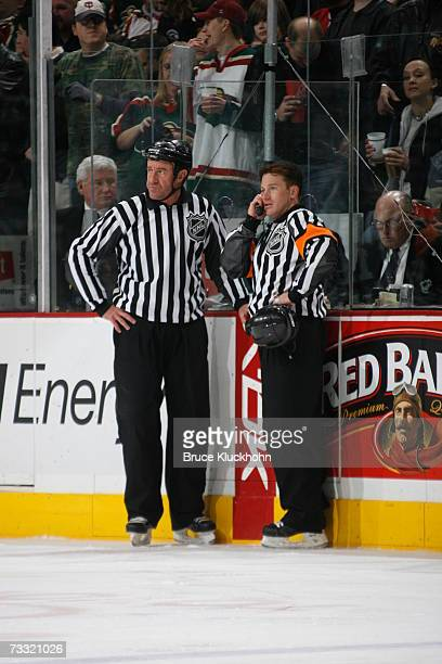 Referee Kelly Sutherland listens on the phone next to linesman Pat Dapuzzo for a review of a goal in action between the Minnesota Wild and the...