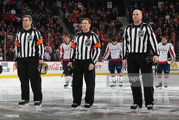 Referee Kelly Sutherland stands at centre ice with Stephane Auger and Michel Cormier during the singing of the national anthems prior to a game...
