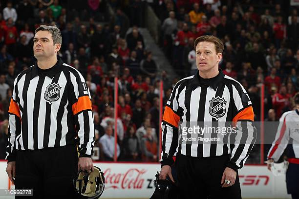 Referee Kelly Sutherland stands at centre ice with Stephane Auger during the singing of the national anthems prior to a game between the Ottawa...