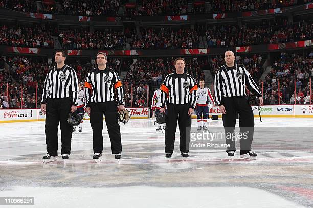 Referee Kelly Sutherland stands at centre ice with Steve Miller Stephane Auger and Michel Cormier during the singing of the national anthems prior to...