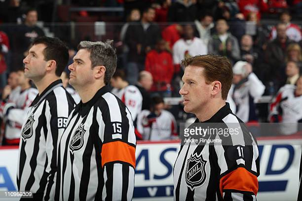 Referee Kelly Sutherland stands at centre ice with Steve Miller and Stephane Auger during the singing of the national anthems prior to a game between...