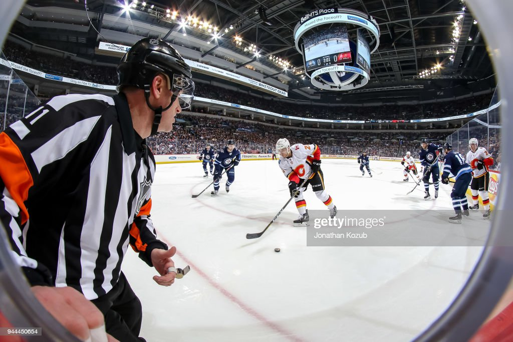 Referee Kelly Sutherland #11 watches as Garnet Hathaway #21 of the Calgary Flames plays the puck while Jacob Trouba #8 of the Winnipeg Jets defends during first period action at the Bell MTS Place on April 5, 2018 in Winnipeg, Manitoba, Canada. The Jets defeated the Flames 2-1.