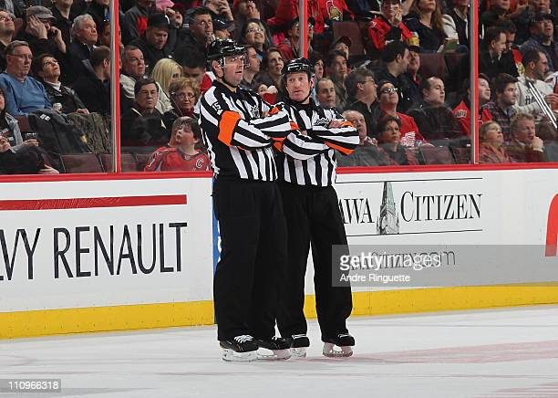 Referee Kelly Sutherland works a game between the Ottawa Senators and Washington Capitals with Stephane Auger at Scotiabank Place on March 25 2011 in...