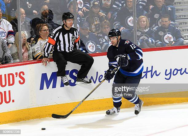 Referee Kendrick Nicholson leaps out of the way of Drew Stafford of the Winnipeg Jets as he plays the puck along the boards during second period...