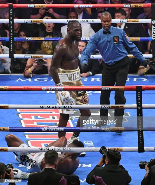 Referee Kenny Bayless directs Deontay Wilder to a neutral corner after he knocked out Luis Ortiz in the seventh round of their WBC heavyweight title...