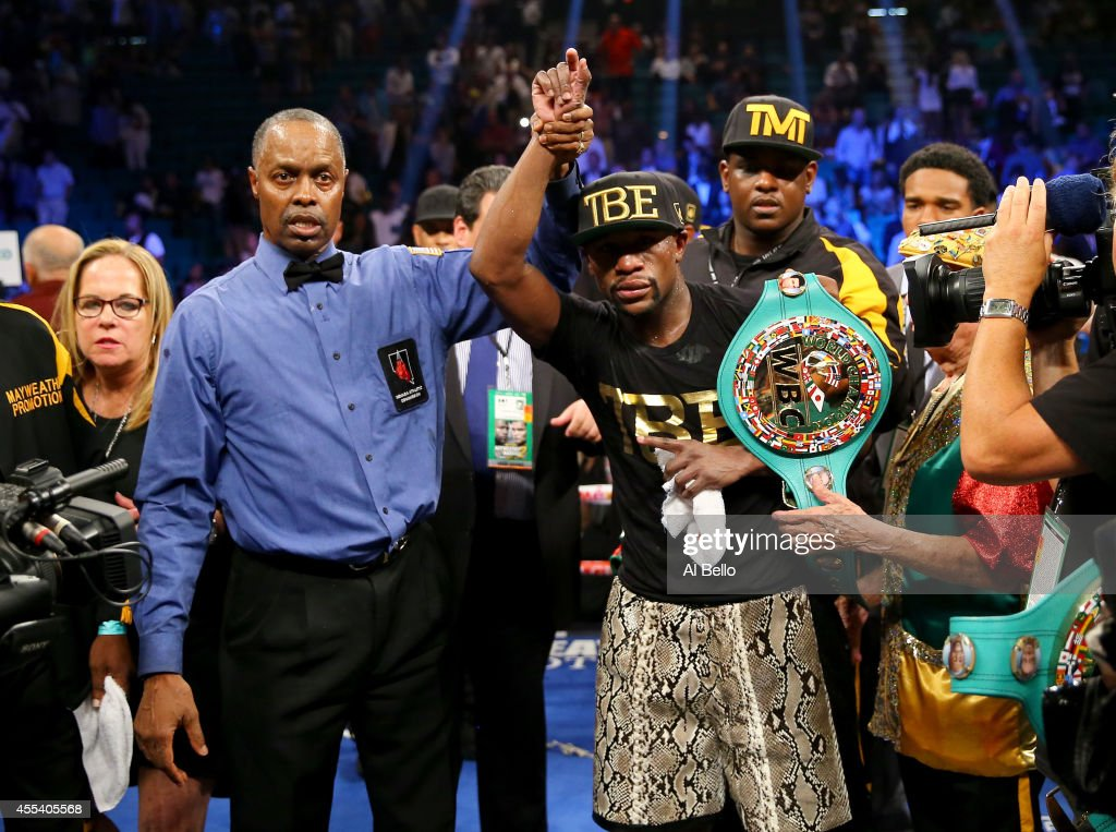 Referee Kenny Bayless (L) holds up Floyd Mayweather Jr.'s hand as he celebrates his unanimous-decision victory over Marcos Maidana during their WBC/WBA welterweight title fight at the MGM Grand Garden Arena on September 13, 2014 in Las Vegas, Nevada.