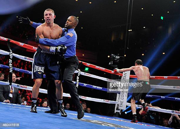 Referee Kenny Bayless leads Matt Korobov aways as he stops the fight as Andy Lee celebrates after their bout for a vacant WBO middleweight title at...