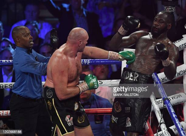 Referee Kenny Bayless stops the fight after the towel was thrown in by Wilder's trainer as British boxer Tyson Fury defeats US boxer Deontay Wilder...