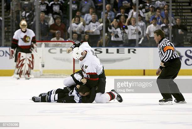 Referee Kerry Fraser skates in as Zdeno Chara of the Ottawa Senators prepares to punch Vincent Lecavalier of the Tampa Bay Lightning as goaltender...