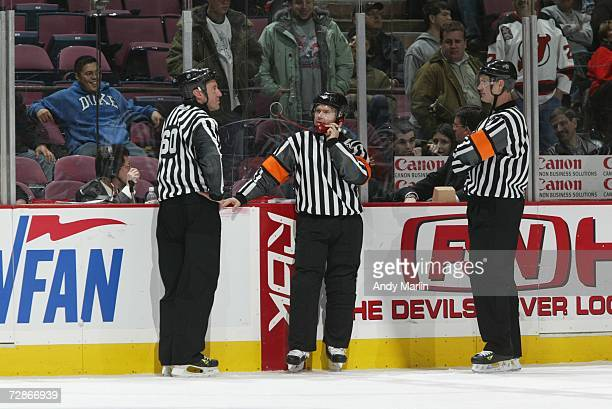 Referee Kerry Fraser talks on the phone while linesman Pat Dapuzzo and referee Dan O'Rourke look on during the New Jersey Devils game against the...