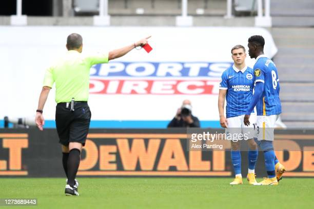 Referee Kevin Friend awards Yves Bissouma of Brighton and Hove Albion a red card following a VAR review of a bad challenge during the Premier League...