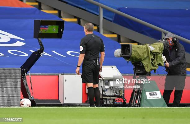 Referee Kevin Friend checks the VAR display before awarding Everton a penalty for a handball during the Premier League match between Crystal Palace...