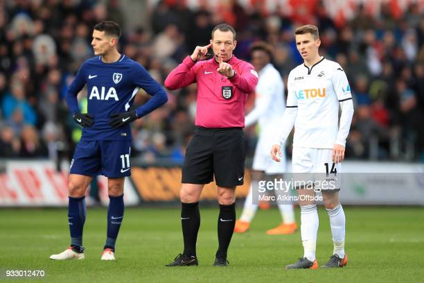 Referee Kevin Friend consults VAR as the players look on during the Emirates FA Cup Quarter Final match between Swansea City and Tottenham Hotspur at...