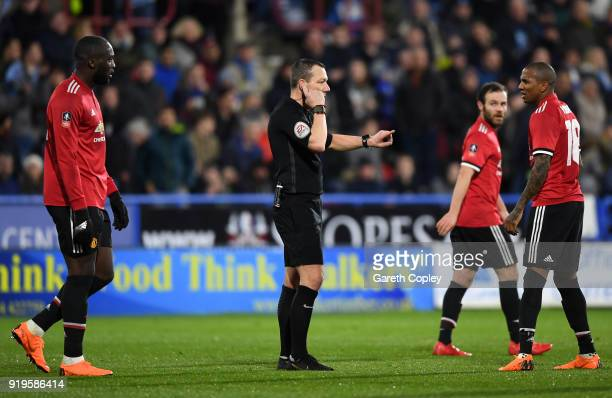 Referee Kevin Friend consults with the Video Assistant Referee as Manchester United players await a decision over a Juan Mata of Manchester United...