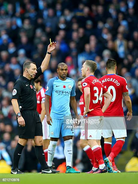 Referee Kevin Friend gives Adam Forshaw of Middlesbrough a yellow card during the Premier League match between Manchester City and Middlesbrough at...