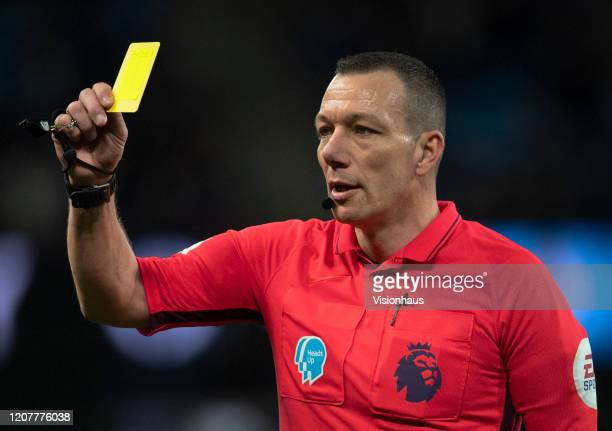 Referee Kevin Friend issues a yellow card during the Premier League match between Manchester City and West Ham United at Etihad Stadium on February 9...