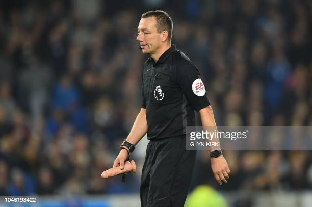 Referee Kevin Friend removes on object which was thrown onto the pitch during the English Premier League football match between Brighton and Hove...