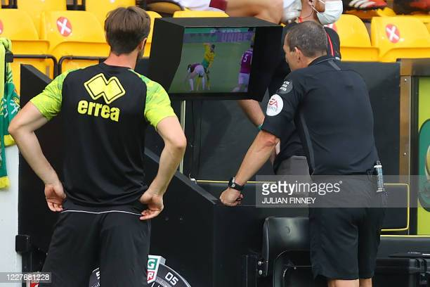 Referee Kevin Friend watches a VAR replay before showing a red card to Norwich City's Argentinian midfielder Emiliano Buendía for elbowing Burnley's...