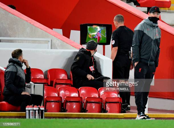 Referee Kevin Friend watches an incident on the VAR review screen to make a decision to disallow a Liverpool goal during the English Premier League...