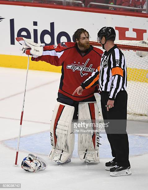 NHL referee Kevin Pollock tells Washington Capitals goalie Braden Holtby to pick his mask up off the ice after throwing it in protest during the...