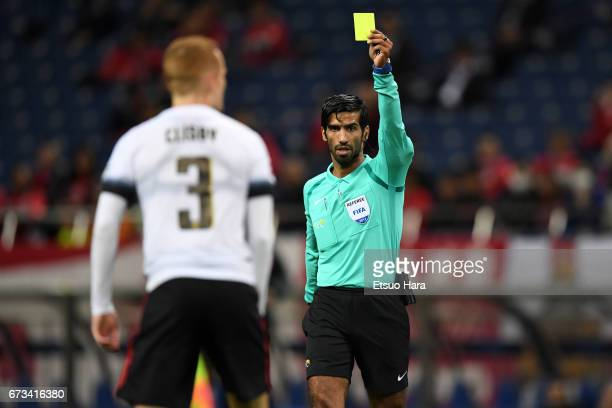 Referee Khamis Mohammed Al Marri shows an yellow card to Jack Clisby of Western Sydney during the AFC Champions League Group F match between Urawa...