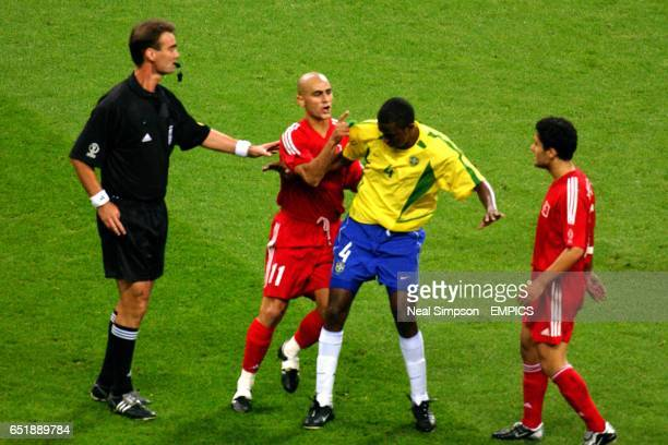 Referee Kim Milton Nielsen steps in to calm down Turkey's Hasan Sas who points an accusing finger at Brazil's Roque Junior as Yildiray Basturk looks...