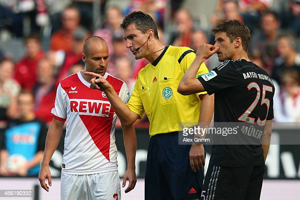 Referee Knut Kircher discusses with Thomas Mueller of Muenchen and Miso Brecko of Koeln during the Bundesliga match between 1 FC Koeln and FC Bayern...