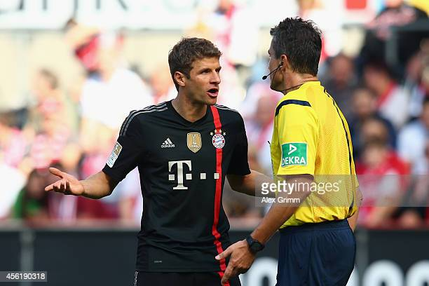 Referee Knut Kircher discusses with Thomas Mueller of Muenchen during the Bundesliga match between 1 FC Koeln and FC Bayern Muenchen at...
