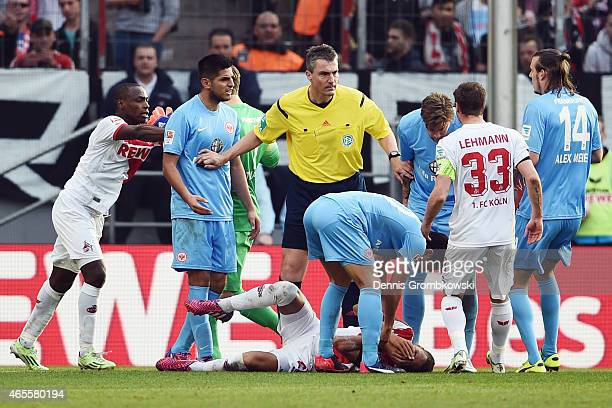 Referee Knut Kircher holds back Carlos Zambrano of Frankfurt as Deyverson of Koeln reacts on the pitch during the Bundesliga match between 1 FC Koeln...