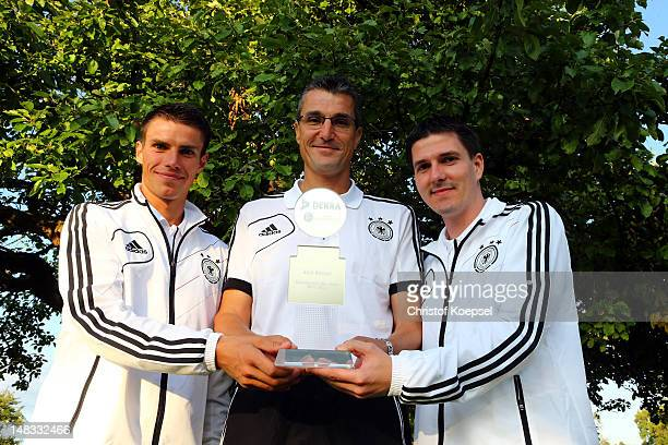 Referee Knut Kircher poses after being voted as the referee of the yera with his assistant referees Robert Kempter and Michael Lupp during the DFB...