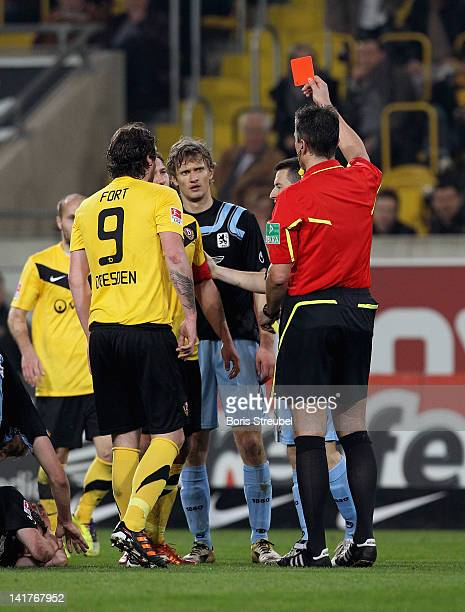 Referee Knut Kircher shows a red card to Robert Koch of Dresden during the Second Bundesliga match between SG Dynamo Dresden and 1860 Muenchen at...