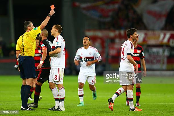 Referee Knut Kircher shows a red card to Xabi Alonso of FC Bayern Muenchen during the Bundesliga match between Bayer Leverkusen and FC Bayern...