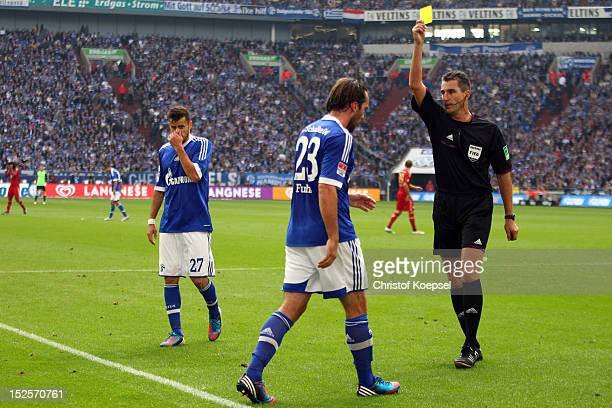 Referee Knut Kircher shows Christian Fuchs of Schalke the yellow card during the Bundesliga match between FC Schalke 04 and FC Bayern Muenchen at...