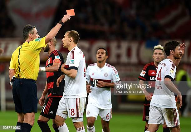 Referee Knut Kircher shows the red card to Bayern Munich's Spanish midfielder Xabi Alonso during the German first division Bundesliga football match...