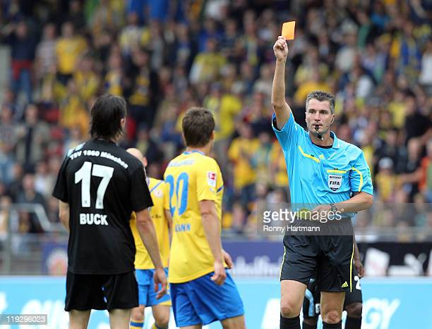 Referee Knut Kircher shows the red card to Stefan Buck of Muenchen during the Second Bundesliga match between Eintracht Braunschweig and TSV 1860...