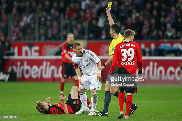 Referee Knut Kircher shows the yellow card to Bastian Schweinsteiger of Bayern after attacking Stefan Kiessling of Leverkusen during the Bundesliga...