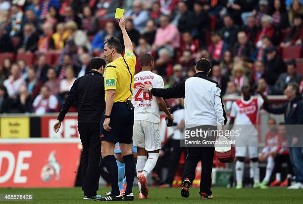 Referee Knut Kircher shows the yellow card to Deyverson of Koeln during the Bundesliga match between 1 FC Koeln and Eintracht Frankfurt at...