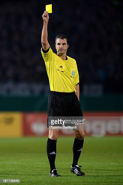 Referee Knut Kircher shows yellow card during DFB Cup second round match between Preussen Muenster and FC Augsburg at Preussenstadion on September 24...