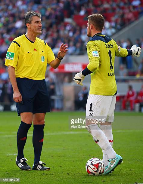 Referee Knut Kircher talks to goalkeeper Timo Horn of Koeln during the Bundesliga match between 1 FC Koeln and FC Bayern Muenchen at...