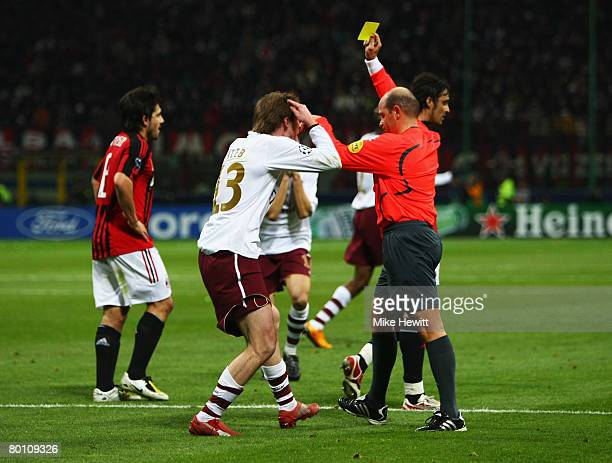Referee Konrad Plautz of Austria shows a yellow card to Aleksandr Hleb of Arsenal for simulation on the edge of the box during the UEFA Champions...
