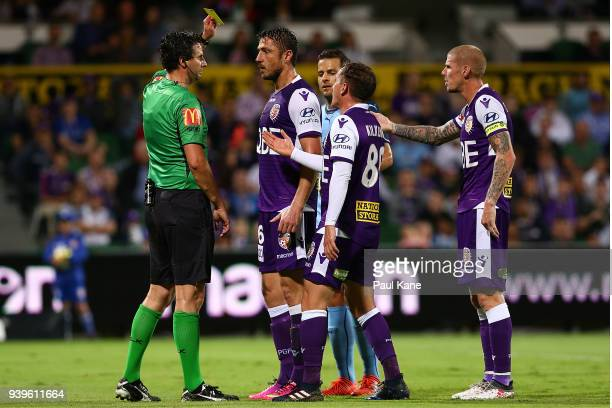 Referee Kris GriffithsJones shows Dino Djulbic of the Glory a yellow card during the round 25 ALeague match between the Perth Glory and Sydney FC at...