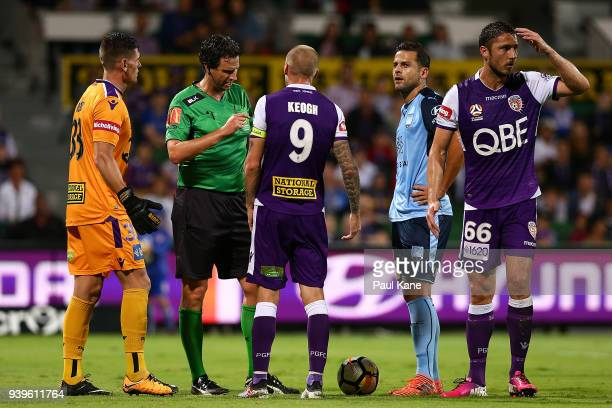 Referee Kris GriffithsJones talks with Andy Keogh of the Glory after issueing Dino Djulbic a yellow card during the round 25 ALeague match between...