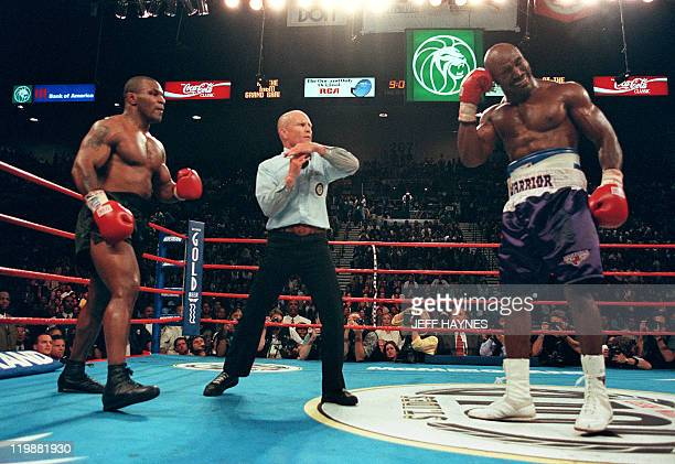 Referee Lane Mills stops the fight in the third round as Evander Holyfield holds his ear as Mike Tyson watches 28 June 1997 during their WBA...
