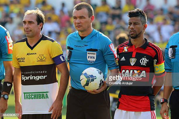 Referee Leandro Pedro Vuaden poses for a photo with captain Paulo Baier of Criciuma and captain Leo Moura of Flamengo before a match between Criciuma...