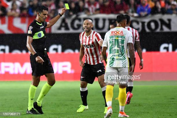 Referee Leandro Rey Hilfer shows a yellow card to Javier Mascherano of Estudiantes during a match between Estudiantes and Defensa y Justicia as part...