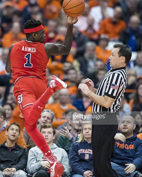 A referee leans out of the way of Bashir Ahmed of the St John's Red Storm as he saves a loose ball from going out of bounds during the first half...
